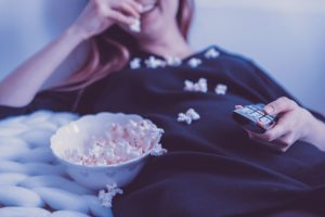 Female watching TV and eating popcorn